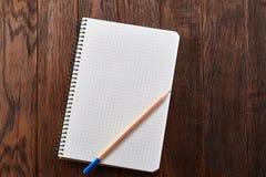 Säubern Sie quadratisches Schreibheft mit gelbem Bleistift auf dunklem hölzernem Weinlesehintergrund, Draufsicht, Bildungskonzept Lizenzfreie Stockfotos
