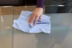 Säubern Sie Tabelle mit Mikrofasertuch Stockfotos
