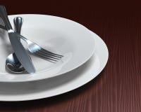 Säubern Sie weiße Teller u. Tischbesteck auf dunklem Woodgraintabulator Lizenzfreies Stockbild