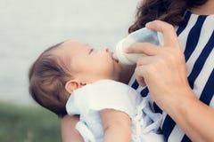 Säuglingsbaby auf durch ihre Trinkmilch der Mutter von der Flasche eingezogen werden Lizenzfreie Stockbilder