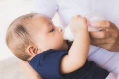 Säuglingsbaby auf durch ihre Trinkmilch der Mutter von der Flasche eingezogen werden Lizenzfreie Stockfotografie