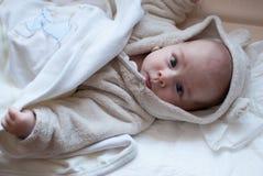 Säuglingsbaby im Bett, das erhält, im Bademantel zu schlafen Stockfoto