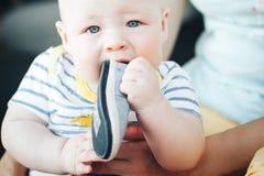 Säuglingsbaby-Kinderjunge, den sechs Monate alte ist-, nimmt seinen Schuh im Mund Stockfoto