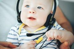 Säuglingsbaby-Kinderjunge sechs Monate alte mit Kopfhörern Stockbilder
