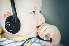 Säuglingsbaby-Kinderjunge sechs Monate alte mit Kopfhörern Lizenzfreie Stockfotos
