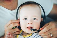 Säuglingsbaby-Kinderjunge sechs Monate alte mit Kopfhörern Stockfotos