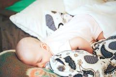 Säuglingsbaby-Kinderjunge sechs Monate alte schläft zu Hause Stockbilder