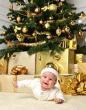 Säuglingsbabykind, das unter Weihnachtsbaum mit Goldkugel deco liegt Stockbild