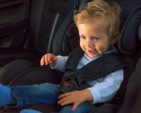 Säuglingsjunge, der in einem Autositz lächelt Stockbild