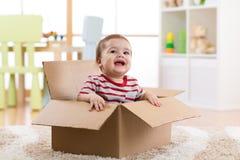 Säuglingsjunge des hübschen Babys, der innerhalb eines Kastens sitzt Lizenzfreie Stockbilder