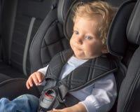 Säuglingsjunge in einem Sicherheitsautositz Stockfoto
