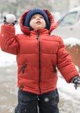 Säuglingsjunge schaut beim Schneien aufwärts Stockfoto