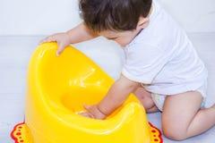 Säuglingskinderbaby-Kleinkindspiel mit kinderleichtem Toilettenschemeltopf auf einem weißen Hintergrund Stockfotos