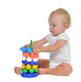 Säuglingskinderbabykleinkind, das in der Hand mit Pyramide spielt Lizenzfreie Stockfotografie