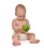 Säuglingskinderbabykleinkind, das in der Windel mit grünem Apfel sitzt Lizenzfreie Stockbilder