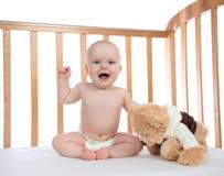 Säuglingskinderbabykleinkind, das in der Windel mit Teddybär bea schreit Lizenzfreie Stockbilder