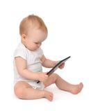 Säuglingskinderbabykleinkind, das digitales Tablette mobi sitzt und schreibt Lizenzfreie Stockfotos