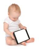 Säuglingskinderbabykleinkind, das digitales Tablette mobi sitzt und schreibt Stockfoto