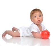 Säuglingskinderbabykleinkind, das mit rotem Ballspielzeug in den Händen spielt Stockfotografie