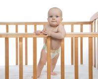 Säuglingskinderbabykleinkind im hölzernen Bett, das oben schaut Lizenzfreie Stockbilder