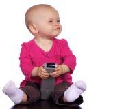 Säuglingsmädchen, das mit einer entfernten Station spielt Lizenzfreie Stockbilder