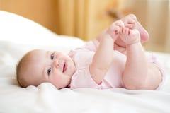 Säuglingsmädchen des lustigen molligen Babys, das mit ihren Füßen spielt Lizenzfreie Stockfotografie