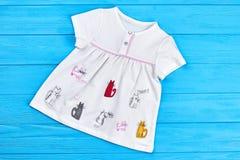 Säuglingsmädchenkleid mit einem Muster von Katzen Stockfotos