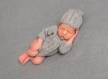 Säuglingsschlafendes in einer gestrickten Ausstattung Lizenzfreie Stockbilder