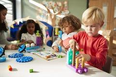 Säuglingsschuljunge, der an einem Tisch unter Verwendung der pädagogischen Bauspielwaren mit seinen Mitschülern, Abschluss oben s stockbild
