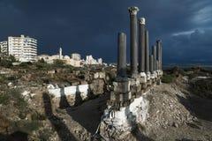 Säulen mit Stadtbild im Sonnenlicht während des Sturms in den Ruinen mit drastischem cloudscape im Reifen, sauer, der Libanon stockbild