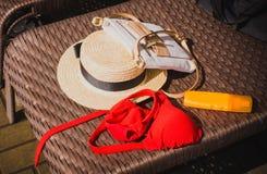 Słomiany kapelusz, torba, czerwony swimsuit i sunscreen na słomianym tle, fotografia stock
