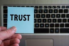 Słowa zaufanie na kleistym nutowym chwycie w ręce na klawiaturowym tle zdjęcie stock