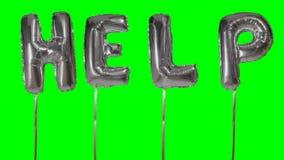 Słowo pomoc od helu srebra balonu listów unosi się na zieleń ekranie - zbiory