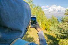 Så härlig kvinna som överst står av ett berg i huven med en ryggsäck _ se bergen och träden Royaltyfria Bilder
