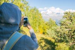 Så härlig kvinna som överst står av ett berg i huven med en ryggsäck _ se bergen och träden Royaltyfria Foton