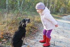 Så! Lyssna till MIG! Utbildning av en hundliten flicka i en björkskog. Arkivbilder