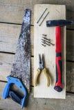 Såg - bågfilen, plattång, skruvar, hammare, spikar - på en stång och träunplaned bräden Royaltyfria Foton