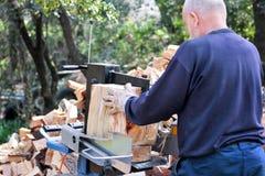 Såg bitande trä för vinter Ett bitande vedträ för man för vintern som använder ett modernt maskinbråte, såg royaltyfri foto