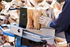 Såg bitande trä för vinter Ett bitande vedträ för man för vintern som använder ett modernt maskinbråte, såg Royaltyfria Bilder
