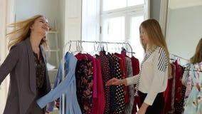 Såg sig inte på länge Den härliga unga kvinnan väljer kläder i shoppar och möter hennes kvinnliga vän stock video