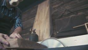 Såga ett stycke av trä med en cirkelsåg på arbetsbänken stock video