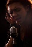 Sångare framme av enmode mikrofon Arkivbilder