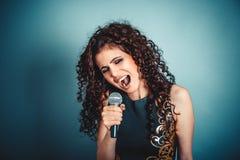 sångare Kvinnadamflicka som sjunger med att sjunga för mikrofon arkivbild