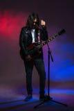 Sångare med långt hår som sjunger i mikrofon och spelar gitarren Fotografering för Bildbyråer