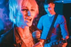 Sångare- och gitarrspelare på etapp under musikbandgig Royaltyfri Bild