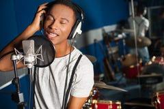 Sångare som antecknar ett spår i studio royaltyfria foton