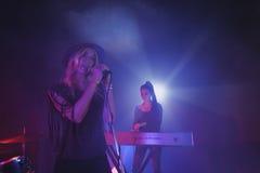 Sångare som sjunger medan musiker som spelar pianot i nattklubb Arkivfoton