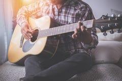 Sångare som spelar gitarren på säng arkivbild