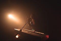 Sångare som spelar pianot, medan utföra i musikkonsert Arkivbild