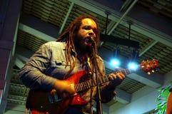 Sångaren för ledning för musikbandet för Reggaemusikbandvägledning Keith Batlin sjunger in i mi Royaltyfri Bild